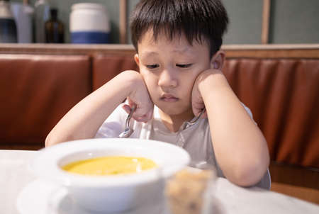 Depressed asian kid boy with anorexia,don't have appetite,child kindergarten bored with food or boredom,refusing to eat vegetable soup,unpalatable,tired of food,nutrition and eating disorder concept