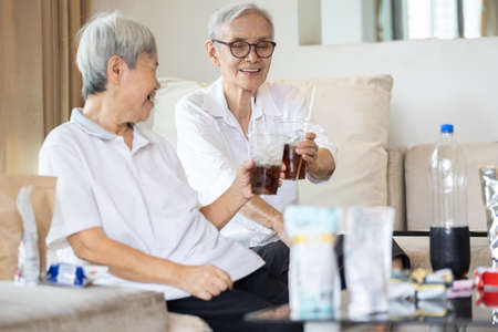 Old elderly people drinking soft drink,eat junk food,snacks on the table at home,asian senior women holding glass of beverages with ice,health care,food consumption and eating behavior concept
