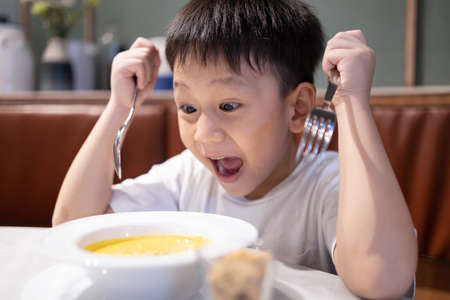 Happy asian kid boy hold spoon and fork,feeling excited and likes to eat,enjoys delicious vegetable soup,child boy with eyes and mouth wide open,tasty food good appetite,healthy meal,nutrition concept