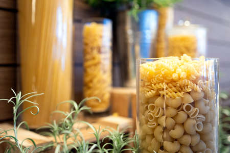 Variety of raw dry pasta in glass jars on a wooden table