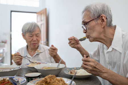 Happy asian senior women eating Thai food,local cuisine,sitting at dining table in the house,old people are enjoying lunch,eat with rice,healthy food,elderly have a good appetite,health care concept