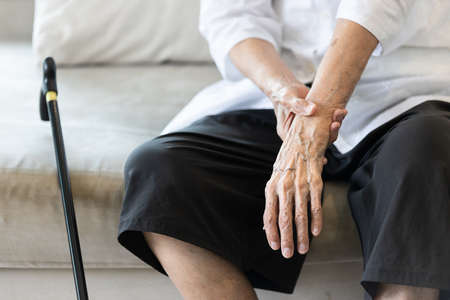 Close up view on the shaking hand of the senior woman,symptom of resting tremor or parkinson's disease,old elderly patient holding her wrist to control hand tremor,neurological disorders,brain problem Stock Photo