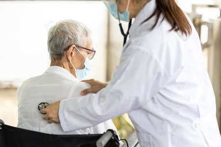 Asian Female doctor listening to sounds from the heart and lungs of senior woman at the back of the body with a stethoscope Standard-Bild