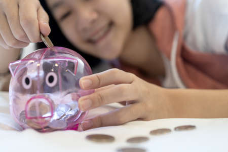 Close up of a coin in the hand,Smiling asian child girl putting coin into piggy bank,feel happy,saving money for the future in education,health care and medical insurance,concept of financial planning Archivio Fotografico
