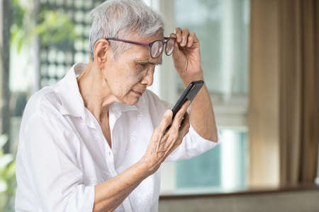 Senior woman with eye glasses, try to read messages on mobile phone