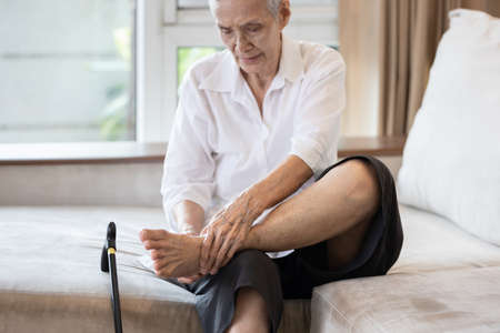 Old elderly with foot injuries,ankle bone diseases,heel pain or soles,asian senior woman suffering from peripheral neuropathy,beriberi,nerve inflammation of the foot, numbness of the feet and toe