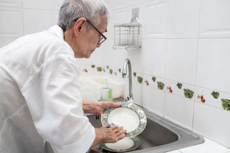 Senior woman or grandmother washing the dishes by hands in the sink,asian elderly clean dirty plates,wash dishes with dishwashing liquid and sponge under running water in a kitchen sink at home