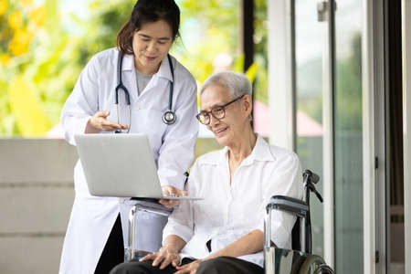 Asian female doctor showing checkup result and explaining to educate medical Information about life planning during consultation with senior patient in a nursing home with laptop computer in her hands