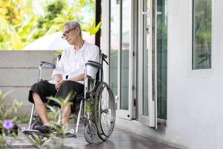 Old elderly patient with disabilities,sit alone in a wheelchair at home,movement disorder,feel lonely,Asian senior people suffering from Alzheimer's disease,dementia,physical or mental health problems
