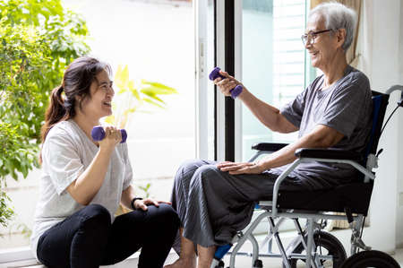 Asian caregiver is doing physical therapy for the old elderly,disabled senior woman in a wheelchair,exercise use dumbbells to help strengthen the muscles of hands,arms and shoulders,workout at home Standard-Bild