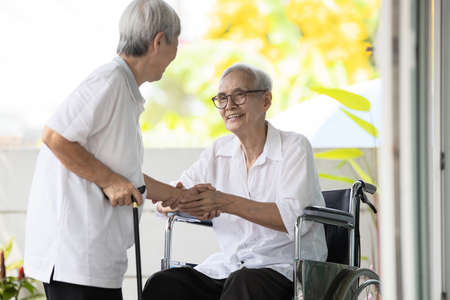 Happy smiling asian elderly woman sit in wheelchair and her old friend meeting at home and shaking hands,disabled senior people greeting and welcoming visiting best friend,warm relations,friendship