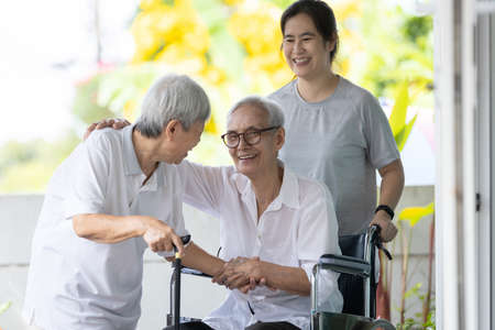 Happy asian elderly woman sit in wheelchair with female caregiver,senior grandmother greeting and welcoming visiting friend or her family embracing enjoy at front door during Christmas holiday at home 版權商用圖片