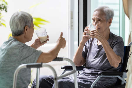 Healthy asian elderly sibling are drinking fresh milk from the glasses,happy senior people showing thumb up while drinking,strengthening the immunity,health care,healthy nutrition,food,drinks concept Zdjęcie Seryjne