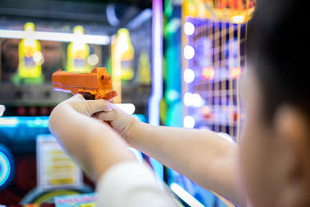 Asian little child playing shooting game for a carnival while visiting in the shopping mall,happy kid boy holding a toy gun in hands,aim and shoot the target,the annual festival at Christmas,New year 版權商用圖片