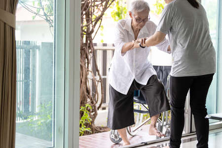 Asian caregiver help care to senior grandmother walk,woman holding hands of the old elderly for support,walking up from a different level floor,safety,prevent accident at nursing home,service concept
