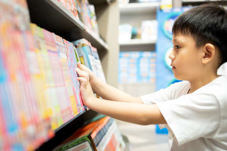 Asian little child selecting book while visiting bookshop,serious kid boy searching and looking for a fairy tale book in bookstore or choose a book from a bookshelf in a public library,reading concept 写真素材