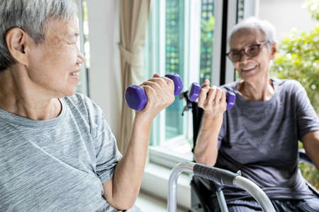 Happy smiling asian senior women exercising together,physical exercise activities by lifting weights,old elderly people with dumbbells,healthy lifestyle,health care,strong and full of energy concept