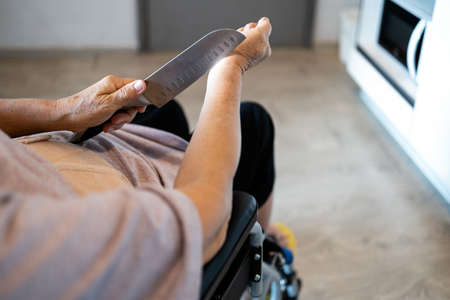 Sick senior woman suffer from depression,debilitating diseases,hopeless,despair from cancer and disability,a crying old people sitting in a wheelchair and holding a knife is about to commit suicide