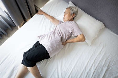 Upset asian senior woman holding hips or waist with her hand while rest in bed,painful facial expression from inflamed muscles,backache,old elderly trying to get up of the mattress after sleep in pain 版權商用圖片