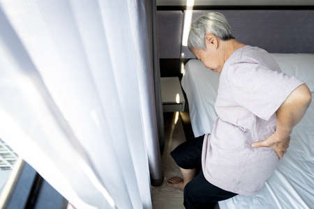 Tired asian senior woman suffering from backache,making effort trying to get up from her bed in the bedroom,old elderly holding her back pain,trying to stand up with difficulty,feeling bad health care
