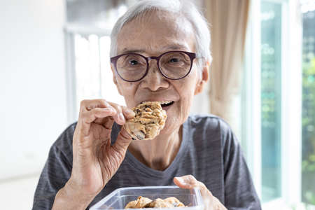 Happy asian senior woman eating chocolate chip cookie or tasting sweet cookie,natural tasty food,delicious snack,old elderly holding a box of cashew nut biscuits in her hand,breakfast in the morning