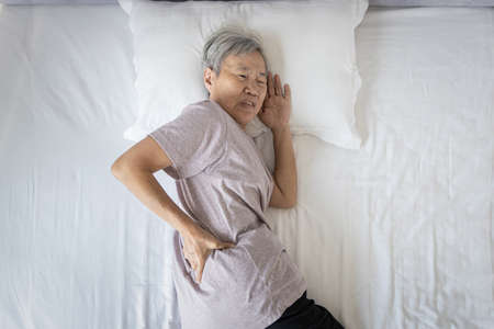 Asian senior woman suffering from backache,sore waist while sleep,unhappy old elderly feeling discomfort pain in her back muscles caused by bad posture or uncomfortable mattress during rest on her bed