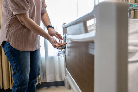 Hands of woman using hand sanitizer before touching a patient on the bed at hospital while visiting,disinfectant bottle for hand washing in room,asian female cleaning hands with alcohol antiseptic gel