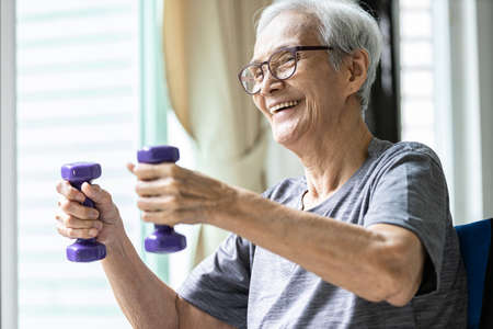 Strong asian senior woman working out,lifting dumbbell weights for strength training,old elderly using dumbbells while exercising,physical therapy in nursing home,health care,healthy lifestyle concept