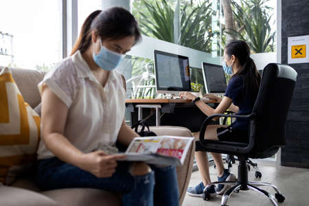 Social Distancing,Asian woman wearing medical protective mask sitting and waiting  to use a computer in public to safety,stop spread COVID-19,keeping distance for infection risk of Coronavirus disease