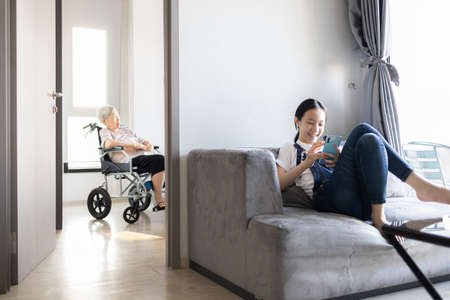 Asian girl obsessed with gadgets overuse social media or addicted to playing online games on mobile phone,ignoring her senior grandmother, sad elderly woman sitting alone feels lonely,family problems