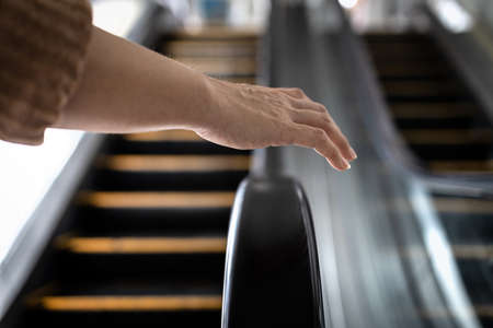 Avoid and Don't touch with objects that are frequently touched for safety,hand of girl was about to touch the handrail of escalator at risk of Coronavirus infection,contaminated with germs or COVID-19