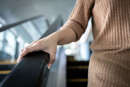 Hand of young woman touching the escalator during  virus pandemic,risk of contagious or contamination  virus,bacteria or germs avoid touching handrail of escalator in public places