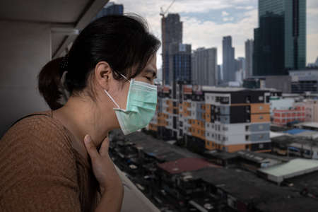 Sad asian woman in a face mask suffer from cough because of air pollution,girl wearing medical protective mask on her face in the city street,concept of pollution,PM2.5,dust allergies and health care 版權商用圖片