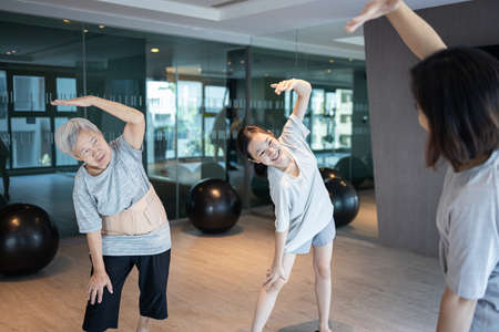 Healthy old elderly exercise with her asian family,happy mother daughter and senior grandmother doing yoga exercise,practicing fitness,stretching in morning,vigorous physical,daily workout good health 版權商用圖片
