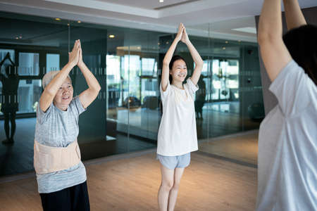 Asian woman doing exercise activity for the old elderly and child girl,family work out at leisure during COVID-19 Coronavirus pandemic,healthy senior,fitness for health care,daily workout in the gym 版權商用圖片