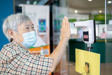 Asian senior woman using infrared digital thermometer measurement,body temperature screening with her palm,old elderly measuring fever at check point for COVID-19,register before entering the hospital