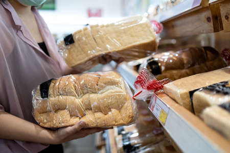 Hands of girl holding sliced white bread product,choosing wheat bread in plastic bag packaged,fresh homemade baked bread in the bakery shop while shopping food,woman buying or selecting food quality 版權商用圖片