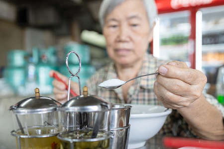 Asian senior woman was using a spoon to scoop white sugar into her bowl of noodles,add flavor to food,eat too much sugar or sweet taste,harm from eating,unhealthy nutrition,concept of obesity,diabetes 版權商用圖片