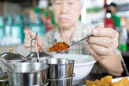 Old elderly eat food that tastes hot spicy,add flavor to food with chili powder from condiment,asian senior woman using a spoon to scoop cayenne pepper into her noodles,harm from eating hot spicy food