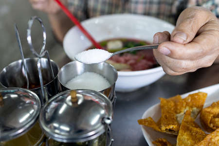 Hand of senior woman holding spoon full of white cane sugar,old elderly eat food that tastes sweet,people scooping sugar from condiment into her bowl of noodles,seasoning,flavoring food with sugar