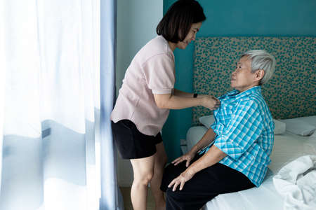 Asian female caregiver taking care of helping elderly patient get dressed,wearing clothes,button up on the shirt for happy senior grandmother,look after old people,support,daily life in a nursing home