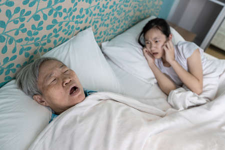 Asian senior woman snoring loudly,open mouth,comfortably sleeping,danger of obstructive sleep apnea disease,stressed child girl wakes up,closing ears with hands,annoying snoring of elderly people