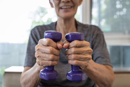 Close Up,hands of senior people holding dumbbells while working out,old elderly lifting dumbbell weights,daily workouts at home,exercise regularly,health care,healthy lifestyle and strong concept 版權商用圖片