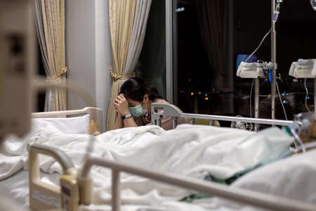 Sad daughter wear face mask watching over sick senior mother in a respirator,crying and tears eyes during look after old elderly in a coma sleep in hospital bed,asian woman praying for cancer patient