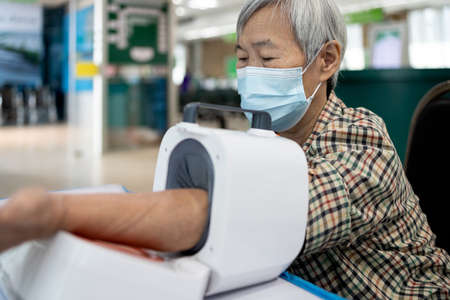 Asian senior people check blood pressure disease,old elderly using digital blood pressure meter measuring pressure of the blood in the circulatory system and rate of the heartbeat,physical examination