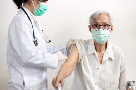 Asian doctor with syringe doing injection of vaccine,nurse vaccinating elderly in the hospital,vaccination to old senior at risk of Coronavirus infection to stimulate immunity against COVID-19 disease