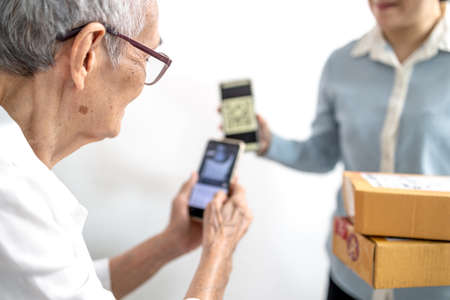 Asian senior woman receiving parcel post box from delivery service,paying deliver with smartphone to scan QR code payment purchase,pay without money,contactless cashless society,old elderly technology