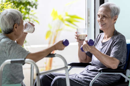Disabled old elderly people in a wheelchair drinking beverages,dietary supplements,healthy senior woman holding glass of fresh milk,exercising in the morning with her friend for health in nursing home Stock Photo