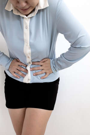 Asian young woman was standing,leaning forward,holding her hands on stomach with severe abdominal pain,painful expression,female office worker suffering from stomachache,irregular menstruation problem Stock Photo