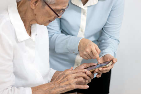 Asian woman teaching the old people how to use mobile phone,senior grandmother learning to use smartphone with a help of adult daughter,learn electronic gadget,study modern technology for elderly Stock Photo